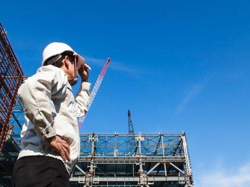 工事現場で青空を見上げる男性